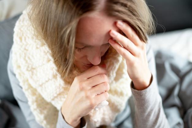 Enfermedad. tratamiento a domicilio. la gripe y el resfriado común. una mujer está enferma en casa, moqueo nasal y gripe.
