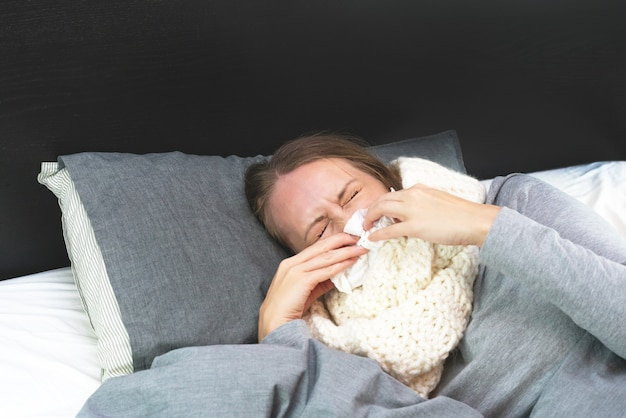 Enfermedad. tratamiento a domicilio. una mujer está enferma en casa, moqueo nasal y gripe. cálidamente vestido y cubierto con una manta.