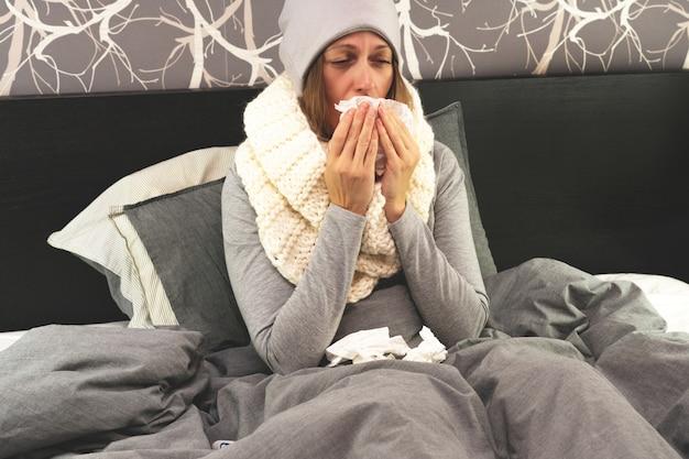Enfermedad. tratamiento a domicilio. una mujer está enferma en casa, secreción nasal y gripe.