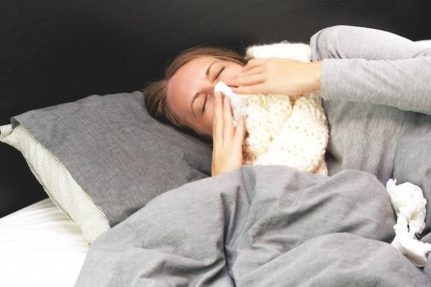 Enfermedad. tratamiento a domicilio. la mujer joven está enferma en casa, secreción nasal y gripe
