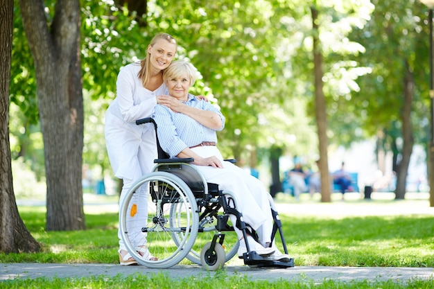 Enfermera abrazando a la anciana en silla de ruedas