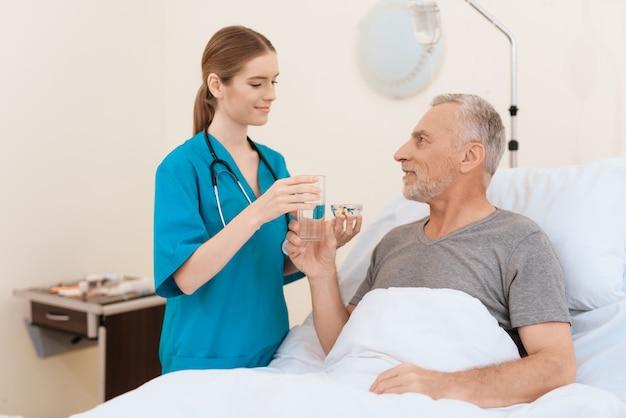 La enfermera se para al lado del anciano y le da agua y pastillas.