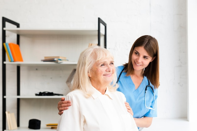 Enfermera y anciana mirando por la ventana
