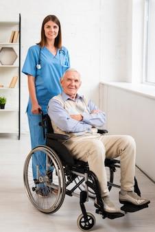 Enfermera y anciano posando mientras mira a la cámara