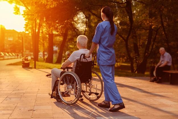 Enfermera y anciano sentado en silla de ruedas mirando la puesta de sol.