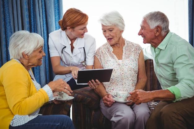 Enfermera apuntando y mostrando la pantalla de una tableta digital a una persona jubilada