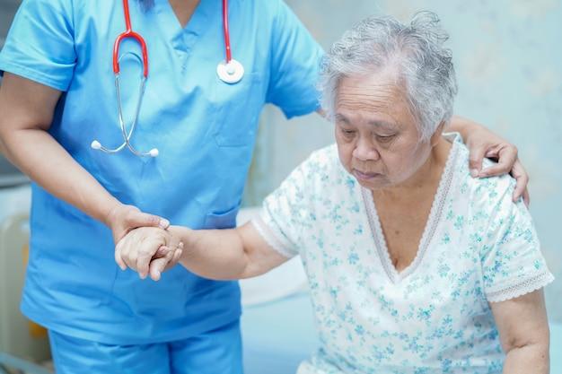 Enfermera asiática, fisioterapeuta, doctora, ayuda y ayuda a una anciana anciana paciente.