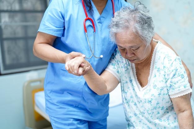 Enfermera asiática, fisioterapeuta, doctora, ayuda y ayuda a anciana anciana paciente.
