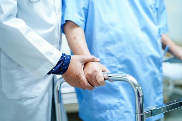 Enfermera asiática, fisioterapeuta, doctora, ayuda y ayuda a un anciano anciano con w