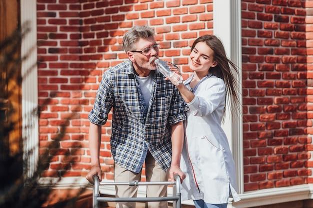 Enfermera atractiva con hombre mayor, dándole agua