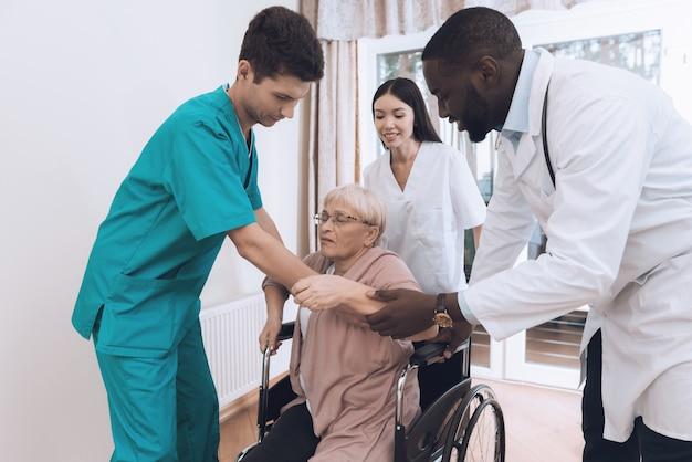 La enfermera ayuda a una anciana a levantarse de la cama.
