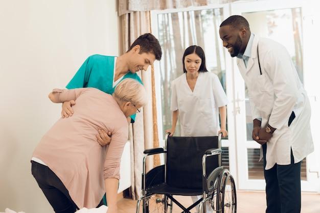 La enfermera ayuda a una anciana a subirse a una silla de ruedas.