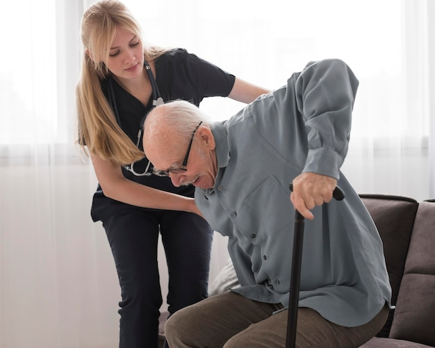 Enfermera ayudando a anciano a levantarse