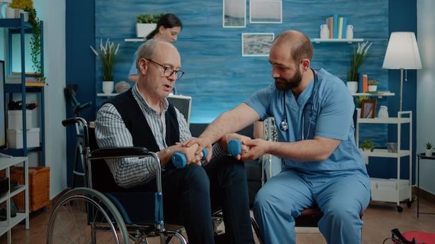 Enfermera ayudando a hombre discapacitado a hacer ejercicio con pesas