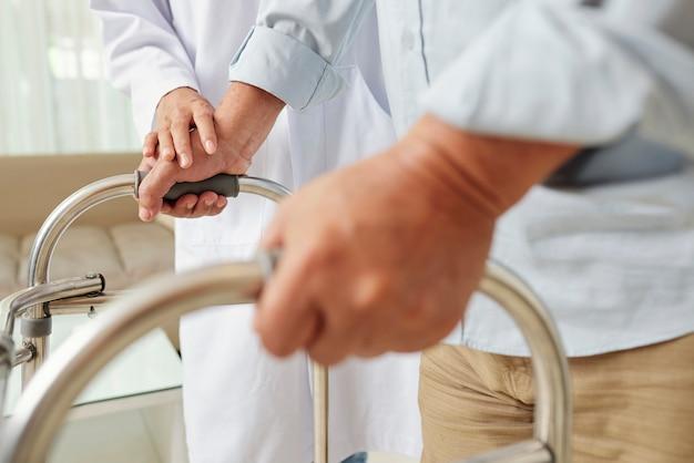 Enfermera ayudando a hombre senior en el hospital Foto Premium