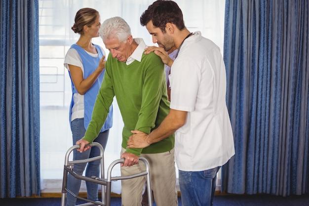 Enfermera ayudando a personas mayores caminando con un andador