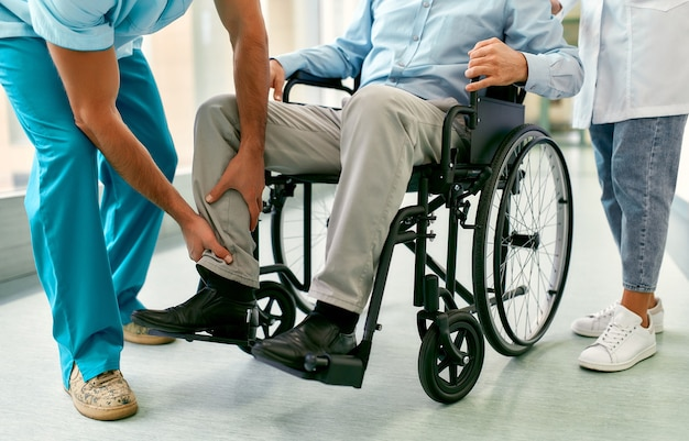 Una enfermera caucásica y un apuesto joven médico en uniforme médico cuidan a un paciente masculino maduro sentado en una silla de ruedas en el hospital.