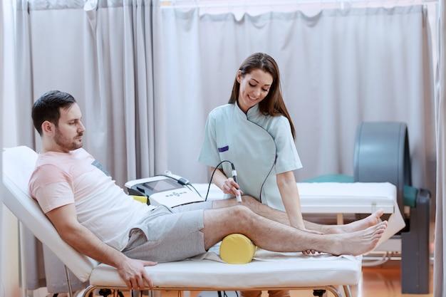 Enfermera caucásica joven que usa un dispositivo de electrólisis para curar a los pacientes con una lesión en la rodilla.
