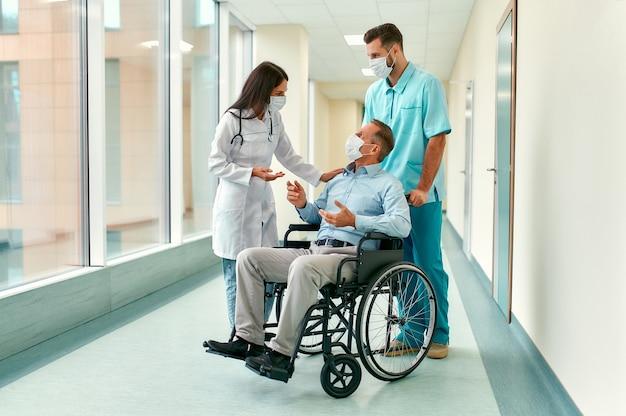 Una enfermera caucásica y un médico joven y guapo con máscaras quirúrgicas para protegerse contra la pandemia de covid 19 cuidan a un paciente masculino maduro sentado en una silla de ruedas en un hospital.