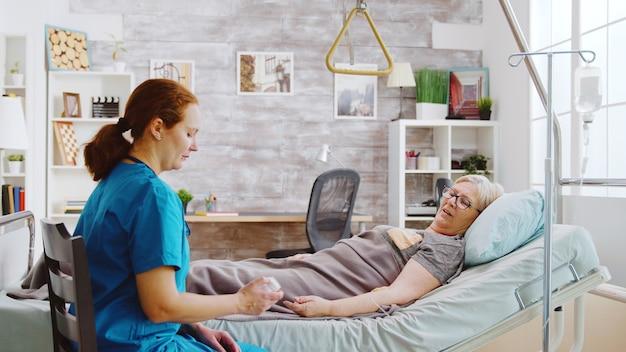 Enfermera caucásica mostrando a una anciana la dosis de píldoras que se supone que debe tomar mientras está acostada en la cama de un hospital en una casa de retiro