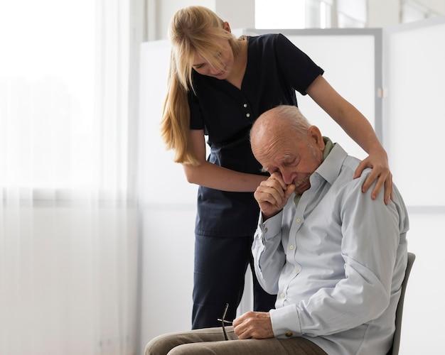 Enfermera consolando anciano llorando