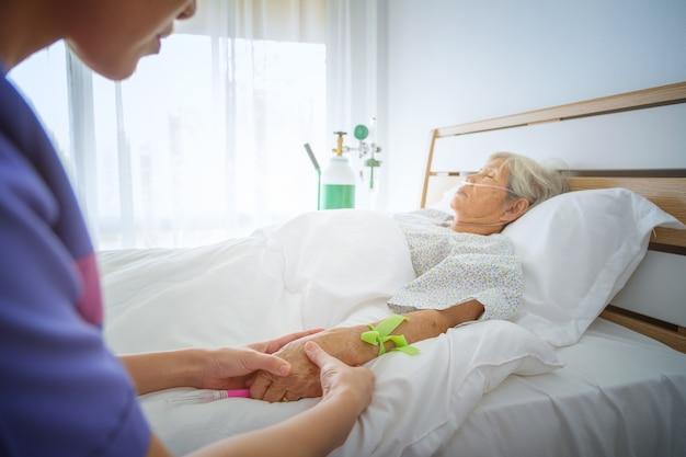 Enfermera controlar pulso mano del paciente en la cama en el hospital