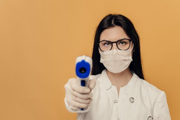 Enfermera en copas. máscara quirúrgica y guantes protectores, sostiene el termómetro, listo para probar debido a la propagación de la pandemia de coronavirus.
