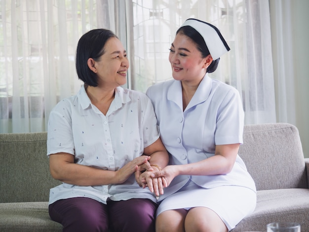La enfermera cuida a los ancianos con felicidad, el cuidador puso su mano sobre la mano de una mujer mayor