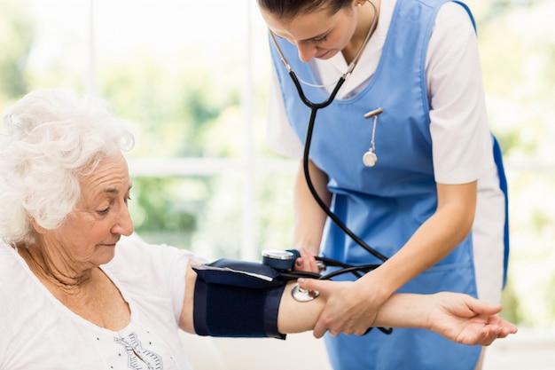Enfermera cuidando enferma anciana en casa