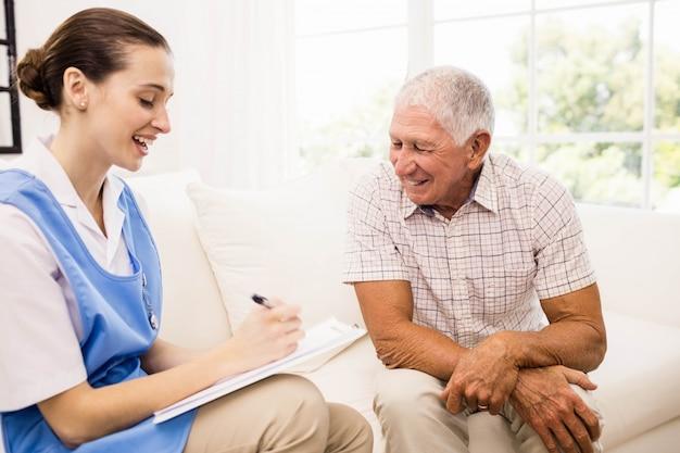 Enfermera cuidando paciente anciano enfermo en casa