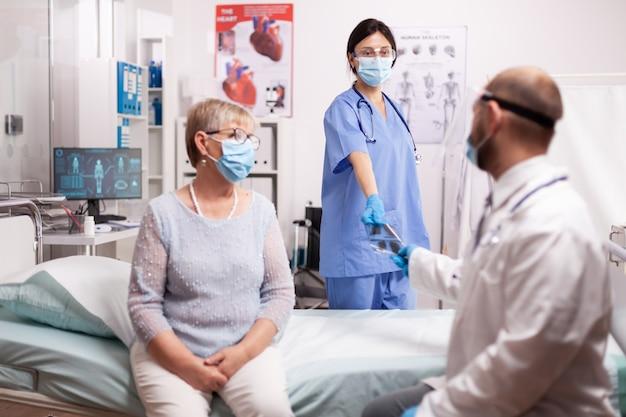 Enfermera dando al médico paciente senior de rayos x usando mascarilla como precaución de seguridad en el curso del brote de covid19