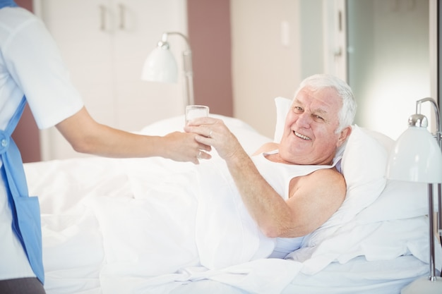 Enfermera dando vaso de agua al hombre mayor