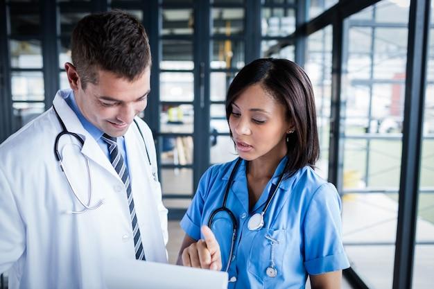 Enfermera y doctor mirando archivos en el pasillo