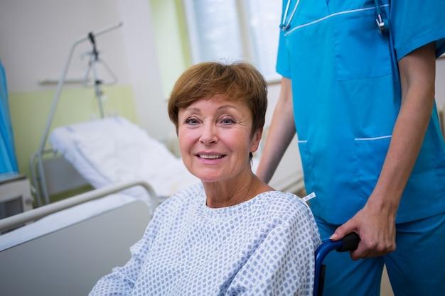 Enfermera empujando a un paciente discapacitado en una silla de ruedas