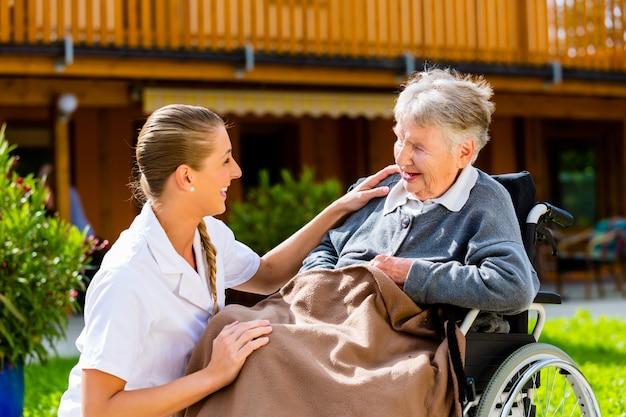 Enfermera empujando a senior mujer en silla de ruedas a pie