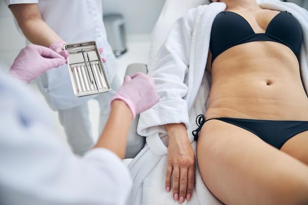Enfermera entregando instrumentos quirúrgicos de acero inoxidable en una bandeja a un médico