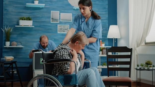 Enfermera con estetoscopio para chequeo de latidos cardíacos en mujer discapacitada