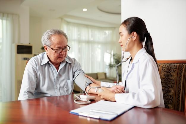 Enfermera examinando al paciente en casa