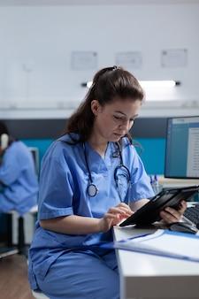 Enfermera farmacéutica mirando tablet pc analizando experiencia en enfermedad