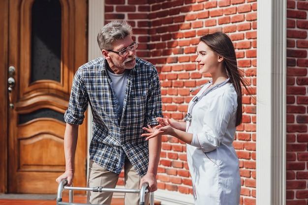 Enfermera hablando con un anciano en silla de ruedas en un hogar de ancianos