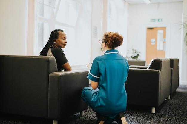 Enfermera hablando con un paciente en la sala de espera.