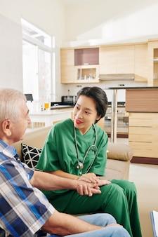 Enfermera hablando con paciente senior en casa