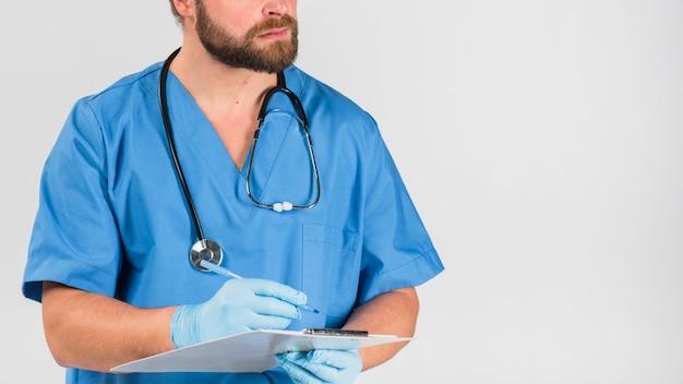 Enfermera hombre sosteniendo y escribiendo en el portapapeles
