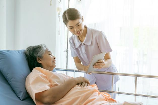 Enfermera informe los resultados del examen de salud para alentar a las pacientes mayores de edad avanzada en el concepto médico-hospitalario