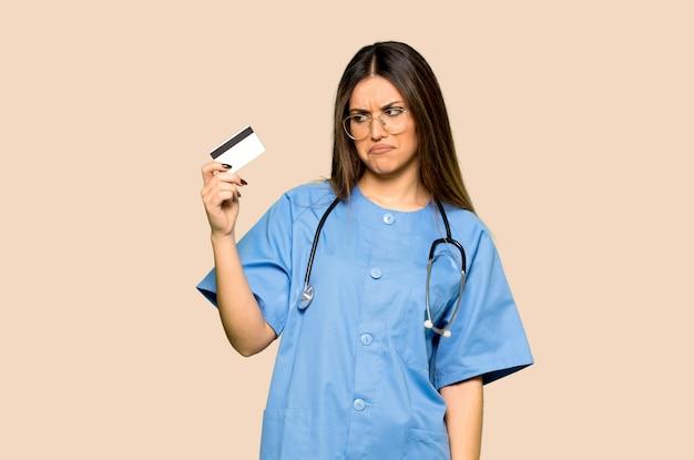 Enfermera joven que sostiene una tarjeta de crédito en fondo amarillo aislado