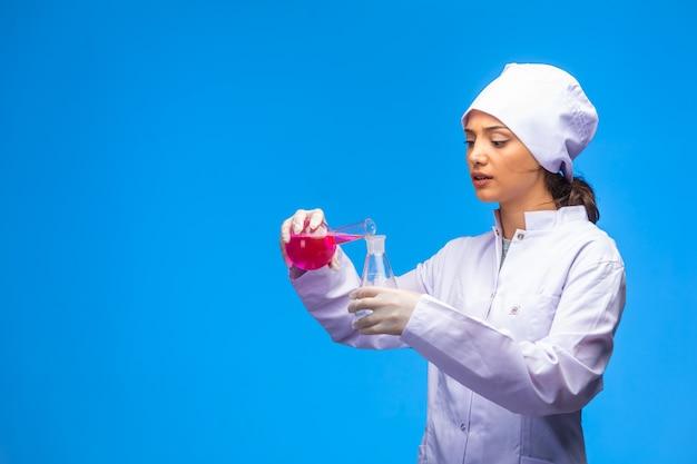 La enfermera joven en uniforme blanco hace la prueba del virus con mucha atención.