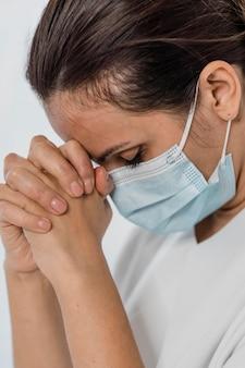 Enfermera con máscara médica rezando