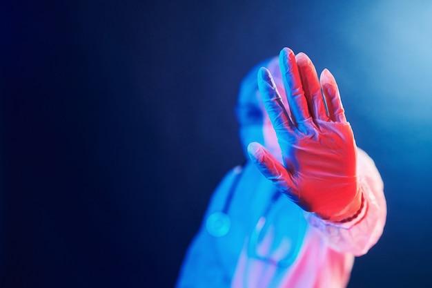 Enfermera en máscara y uniforme blanco de pie en la habitación iluminada de neón y mostrando señal de stop