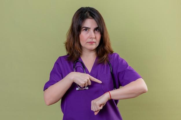 Enfermera de mediana edad con uniforme y con estetoscopio apuntando a su mano recordando el tiempo con expresión escéptica en la cara sobre la pared verde aislada