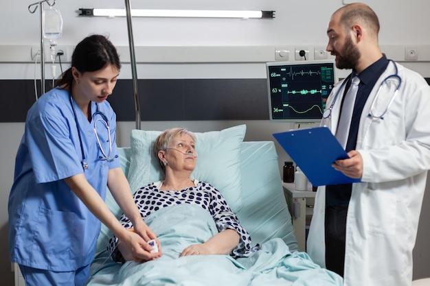 Enfermera médica adjuntando oxímetro en paciente senior